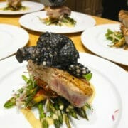 Loin of rare grilled tuna with grilled asparagus tips, topped with a tapioca and squid ink crisp
